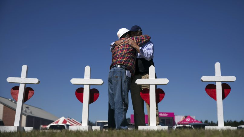 The Rev. Arthur Thomas, right, of Mount Nebo Baptist Church, is embraced by Greg Zanis, who built a cross for each victim of a tornado that killed 23 people and placed them as a makeshift memorial in Beauregard, Alabama, on March 6, 2019. Thomas said several of the dead were members of his congregation. (AP Photo/David Goldman)