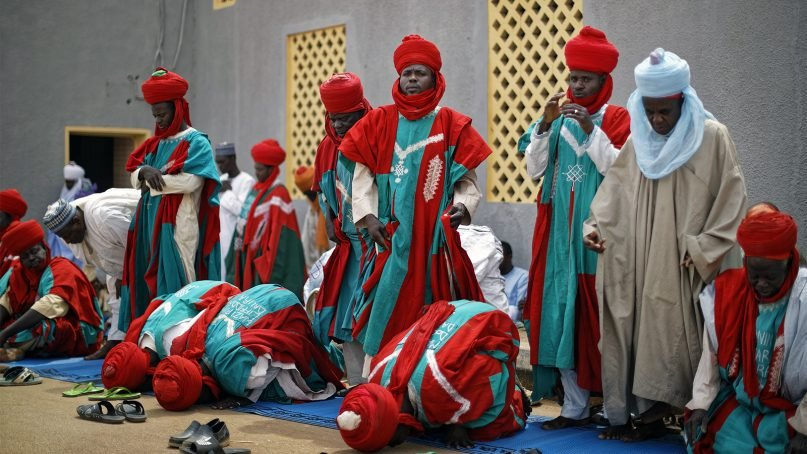 Bodyguards of the emir of Daura make traditional Muslim Friday prayers outside the central mosque as the emir prays inside in Daura, the hometown of President Muhammadu Buhari, in northern Nigeria, on Feb. 22, 2019. Nigerians went to the polls for a presidential election Saturday, Feb. 23, one week after a surprise delay for Africa's largest democracy. (AP Photo/Ben Curtis)