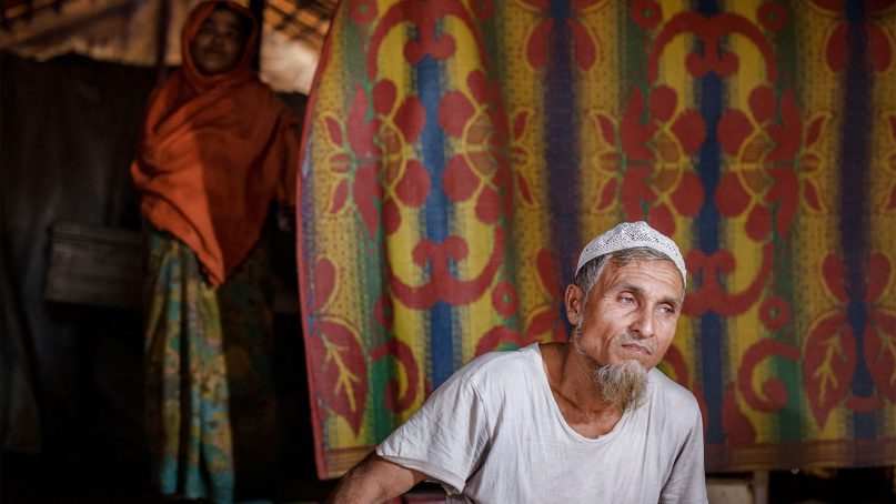 Dil Mohammad sits on the floor of his hut in the Unchiprang refugee camp in souhern Bangladesh on Dec. 11, 2018. Mohammad's wife, rear, helped save him when he attempted suicide. RNS photo by Amir Hamza