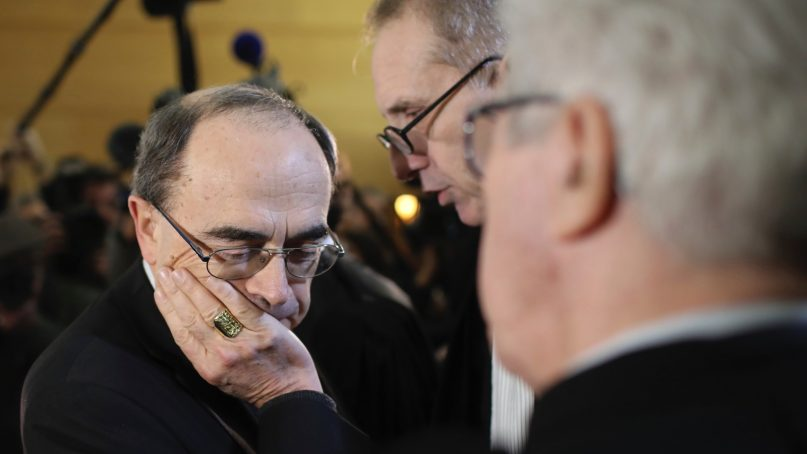 In this Jan. 7, 2019, file photo, Cardinal Philippe Barbarin listens to his lawyers, Jean-Felix Luciani, second right, and Andre Soulier, back to camera, as Barbarin attends the start his trial in Lyon, central France. (AP Photo/Laurent Cipriani, File)