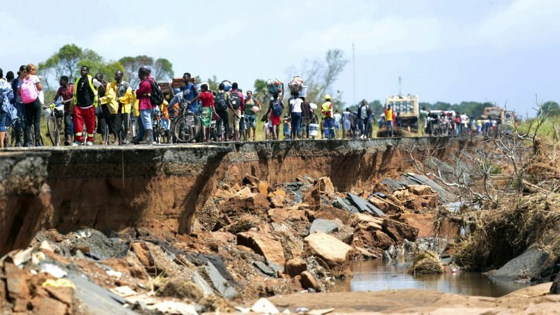 People pass through a section of the road damaged by Cyclone Idai in Nhamatanda, about 30 miles from Beira, in Mozambique, on March 22, 2019. As flood waters began to recede in parts of Mozambique on Friday, fears rose that the death toll could soar as bodies are revealed. (AP Photo/Tsvangirayi Mukwazhi)