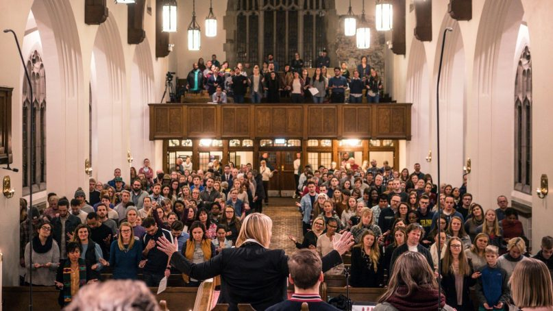 The Rev. Judy Peterson holds her arms out while leading a service. Photo by Karl Clifton-Soderstrom