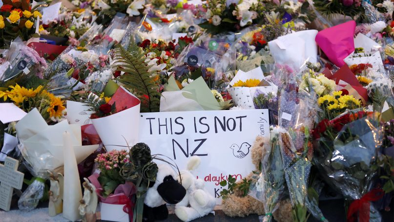 Mourners place flowers as they pay their respects at a makeshift memorial near the Masjid Al Noor mosque in Christchurch, New Zealand, on March 16, 2019. New Zealand's stricken residents reached out to Muslims in their neighborhoods and around the country on Saturday, in a fierce determination to show kindness to a community in pain as a 28-year-old white supremacist stood silently before a judge, accused in mass shootings at two mosques that left dozens of people dead. (AP Photo/Vincent Yu)