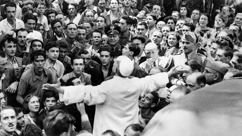 Men, women and soldiers gather around Pope Pius XII, his arms outstretched, during his inspection tour of Rome, Italy, after American air raids in World War II, on Oct. 15, 1943. (AP Photo)