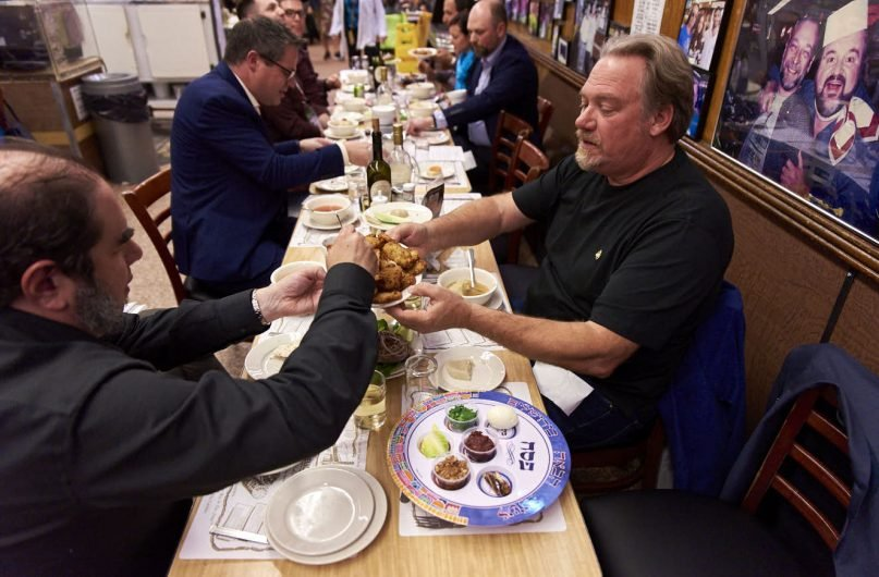 David S. Wallens and Tim Suddard of Classic Motorsports magazine share a plate of latkes during the Jewish Auto Writers Society Passover seder at Katz's Deli in New York on Wednesday, April 17, 2019. RNS photo by Zachary Schulman.