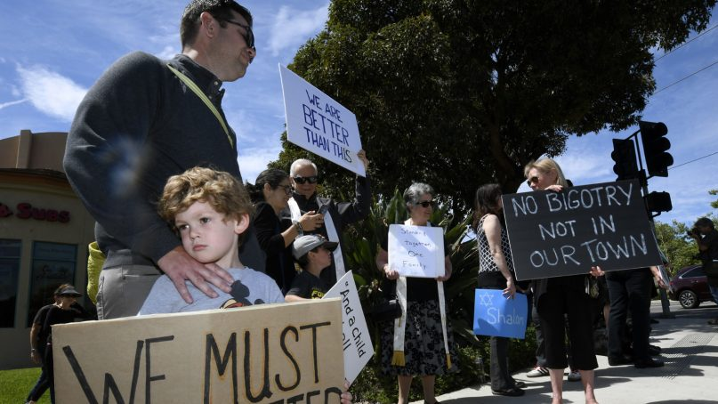 Kyle Fox, 4, and his father, Brady Fox, hold a sign at a vigil April 28, 2019, in Poway, Calif., held to support the victims of Chabad of Poway synagogue shooting. A man opened fire Saturday inside the synagogue near San Diego as worshippers celebrated the last day of Passover. (AP Photo/Denis Poroy)