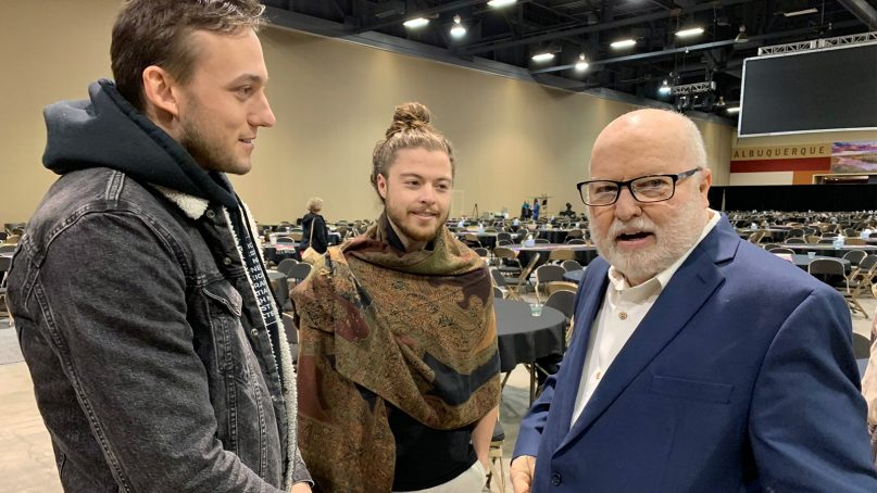 Richard Rohr, right, the 76-year-old Catholic contemplative, mystic and author, visits with Wes Lambert, 27, of Brooklyn, left, and Anthony Graffagnino, 28, of Berkeley, Calif., center, after the close of The Universal Christ conference in Albuquerque, N.M., in March 2019. RNS photo by Cathleen Falsani