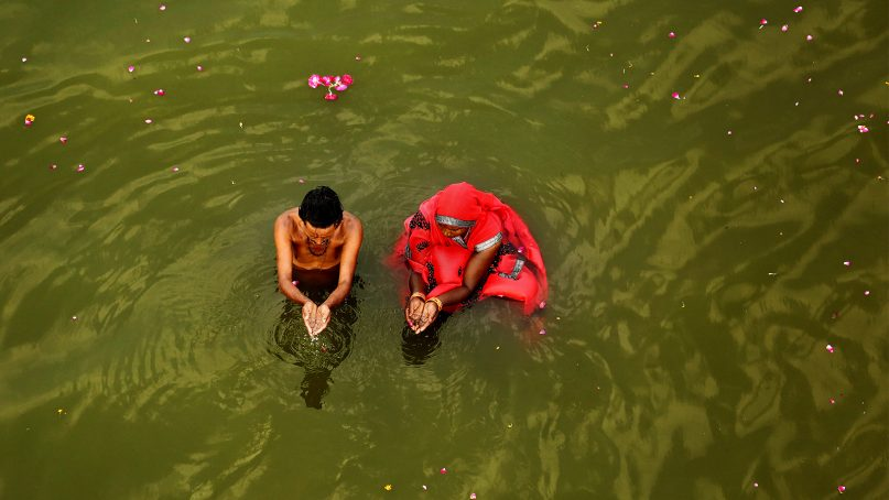 A couple performs morning rituals in the River Ganges on the first day of the nine-day Hindu festival of Navratri on the outskirts of Prayagraj , in the northern Indian state of Uttar Pradesh, India, on April 6, 2019. Hindus are celebrating Navaratri, or the festival of nine nights, with three days each devoted to the worship of Durga, the goddess of valor, Lakshmi, the goddess of wealth, and Saraswati, the goddess of knowledge. (AP Photo/Rajesh Kumar Singh)