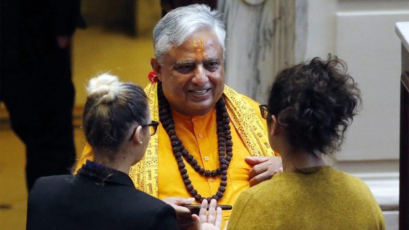 Universal Society of Hinduism President Rajan Zed, center, talks with Oklahoma Senate staffers before delivering a prayer to start the day in the Senate in Oklahoma City, on April 30, 2018. Zed read verses from ancient Sanskrit scriptures that he said date to 1500 B.C. as part of an interfaith week in the legislative body. (AP Photo/Sue Ogrocki)