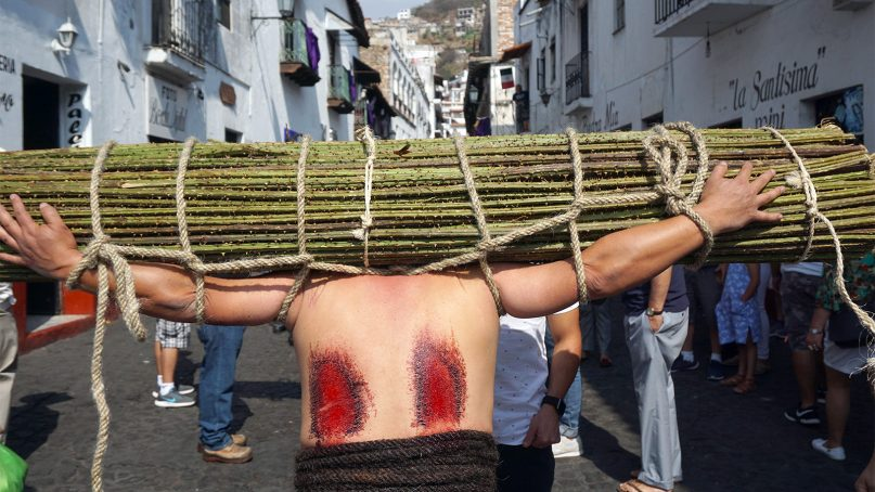 A penitent who is both a Flagelente and an Encruzado processes through Taxco, Mexico, during annual Holy Week festivities that go back centuries. Some bundles of blackberry stems can weigh more than 100 pounds. RNS photo by Irving Cabrera Torres