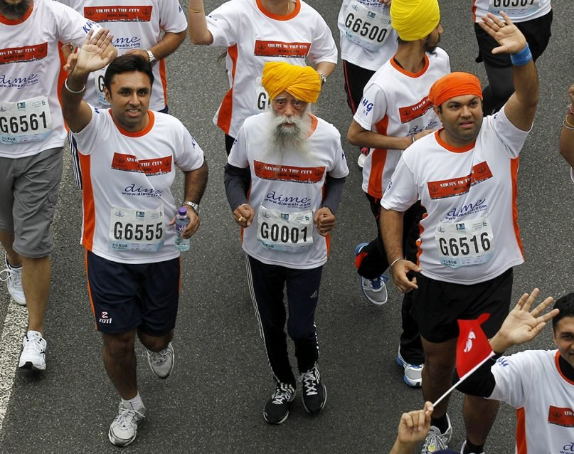 Centenarian marathon runner Fauja Singh, center, originally from Beas Pind, in Jalandhar, India, but who now lives in London, runs in a 10-kilometer race, held as part of the annual Hong Kong Marathon, in Hong Kong, on Feb. 24, 2013. (AP Photo/Kin Cheung)