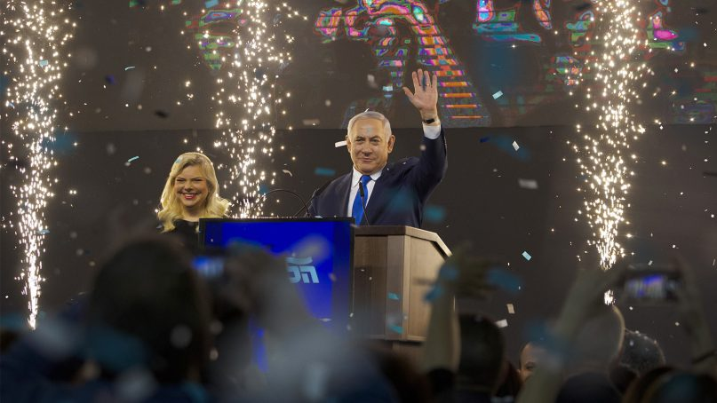 Israeli Prime Minister Benjamin Netanyahu, accompanied by his wife, Sara, waves to supporters after polls closed for Israel's general elections, in Tel Aviv, Israel, on April 10, 2019. (AP Photo/Ariel Schalit)
