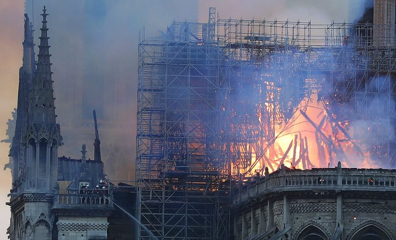 Firefighters, left, tackle the blaze as flames and smoke rise from Notre Dame Cathedral as it burns in Paris on April 15, 2019. (AP Photo/Thibault Camus)