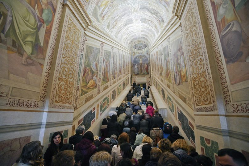 Faithful kneel on the Holy Stairs (Scala Sancta), which, according to the Catholic Church, is the stair on which Jesus Christ stepped on his way to the crucifixion, during a special opening, in Rome, on April 11, 2019. (AP Photo/Andrew Medichini)