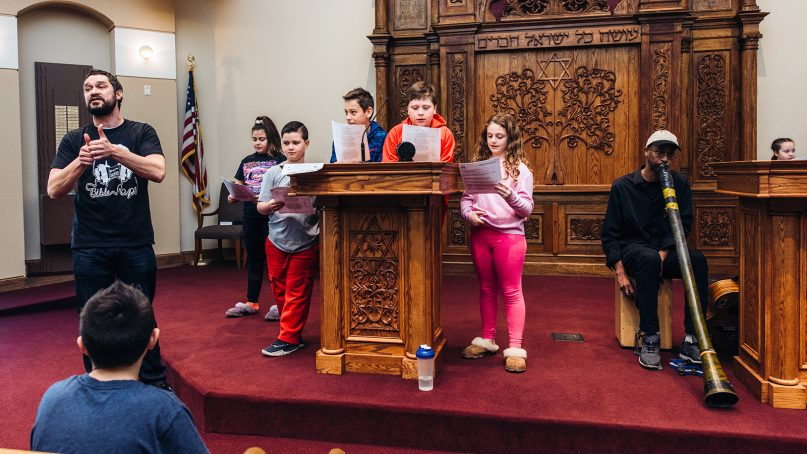 Matt Bar, left, and Ali Richardson, right, perform educational music with youth during a Bible Raps session at a synagogue. Courtesy photo