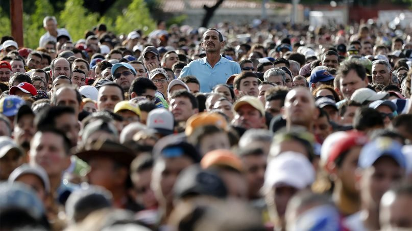 A Venezuelan man stands over the crowd waiting to cross the border into Colombia through the Simon Bolivar bridge in San Antonio del Tachira, Venezuela, on July 17, 2016. (AP Photo/Ariana Cubillos)