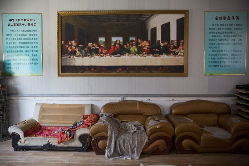 In this photo taken June 4, 2018, a painting of the Last Supper is seen next to posters quoting China's constitution on religious freedom in a house church shut down by authorities near the city of Nanyang in central China's Henan Province. Under President Xi Jinping, China's most powerful leader since Mao Zedong, believers are seeing their freedoms shrink dramatically even as the country undergoes a religious revival. Experts and activists say that as he consolidates his power, Xi is waging the most severe systematic suppression of Christianity in the country since religious freedom was written into the Chinese constitution in 1982. (AP Photo/Ng Han Guan)