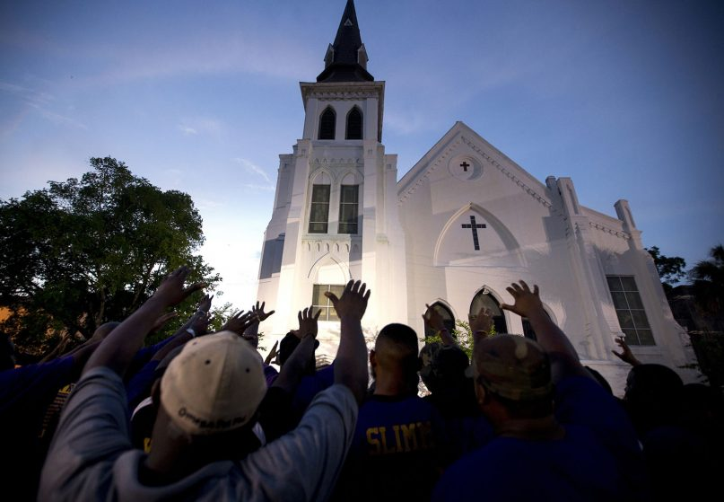 The men of Omega Psi Phi Fraternity Inc. lead a crowd of people in prayer outside the Emanuel AME Church on June 19, 2015, after a memorial in Charleston, S.C. (AP Photo/Stephen B. Morton)