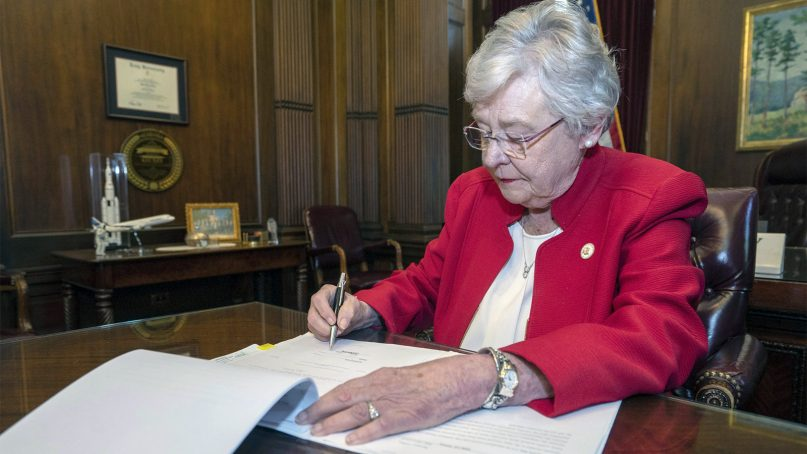 Alabama Gov. Kay Ivey signs a bill that virtually outlaws abortion in the state on May 15, 2019, in Montgomery, Ala. Republicans who support the measure hope challenges to the law will be used by conservative justices on the U.S. Supreme Court to overturn the Roe v. Wade decision that legalized abortion nationwide. (Hal Yeager/Alabama Governor's Office via AP)