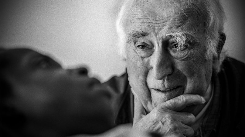 Jean Vanier visits Sebastien, a young man whose injuries in a car accident left him with profound cognitive and physical disabilities, at the L'Arche care home in Trosly-Breuil, France, in 2015. Photo courtesy of Summer in the Forest/R2W Films