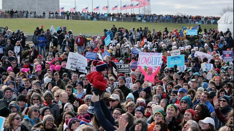 The March for Life crowd smiles as man holds up a child at the rally on Jan. 27, 2017, in Washington, D.C. RNS photo by Adelle M. Banks