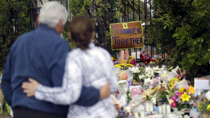 A couple embrace near a growing memorial across the street from the Chabad of Poway synagogue in Poway, Calif., on April 29, 2019. A gunman opened fire, killing one person, on April 27, 2019, as about 100 people were worshipping. The attack happened exactly six months after a mass shooting in a Pittsburgh synagogue. (AP Photo/Greg Bull)