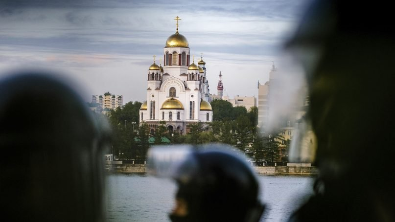 Riot police stand next to demonstrators gathered in front of a newly built fence during a protest against plans to construct a cathedral in a park with the Church on the Blood, a cathedral erected on the place where the last czar, his wife Alexandra and their five children were executed in 1918, in Yekaterinburg, Russia, Wednesday, May 15, 2019. (AP Photo/Anton Basanayev)