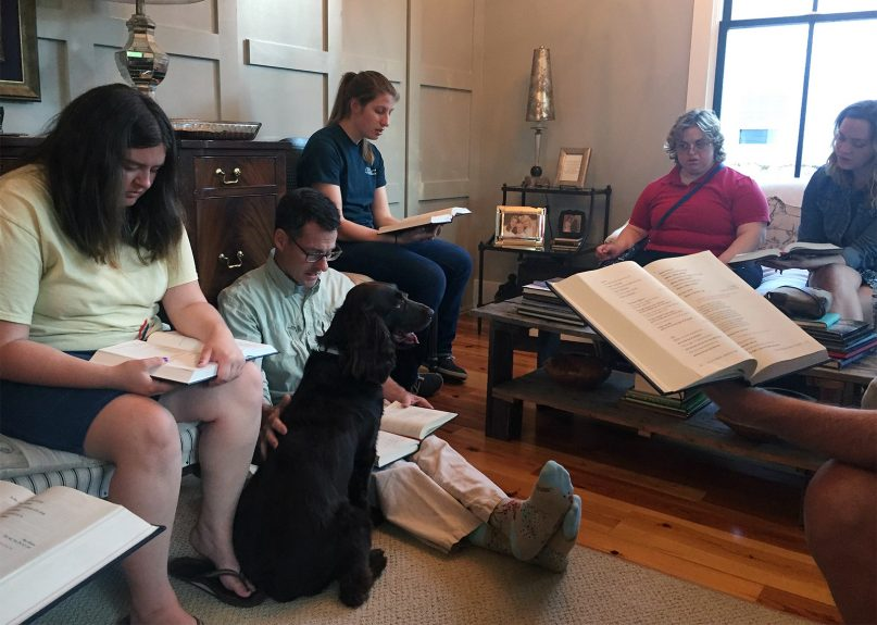 A prayer gathering of Friendship House in Fayetteville, N.C. Scott Cameron sits on the floor beside his dog. RNS photo by Yonat Shimron