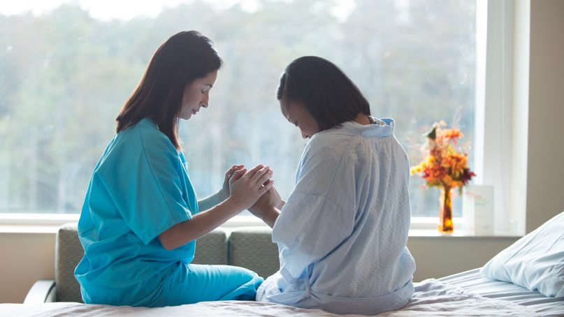 A hospital employee prays with a patient. Photo courtesy of Creative Commons