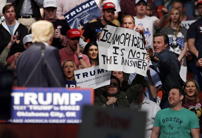 In this Feb. 26, 2016 file photo, then-Republican presidential candidate Donald Trump, left, looks on as a Trump supporter reaches for a sign that reads