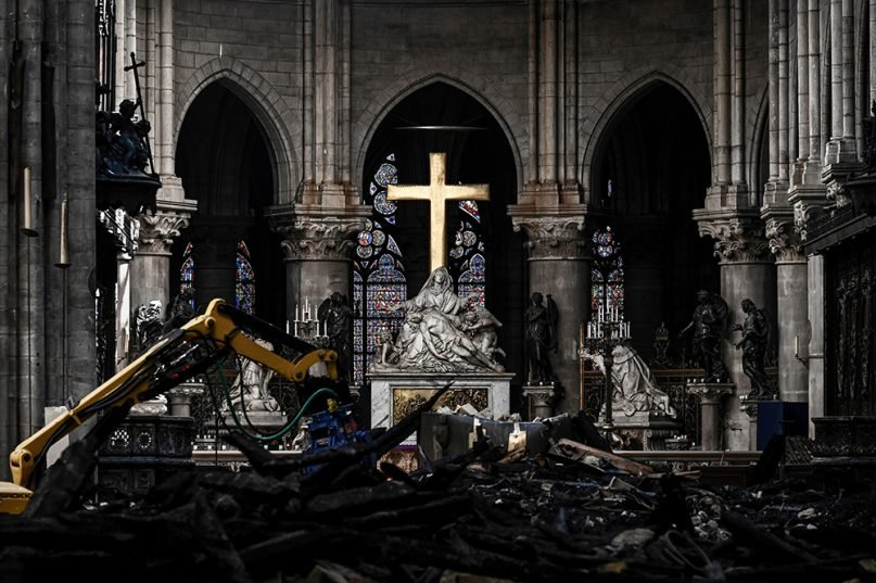 A machine removes rubble below the Pieta sculpture and a cross inside the Notre Dame Cathedral on May 15, 2019, in Paris. (Philippe Lopez/Pool via AP)