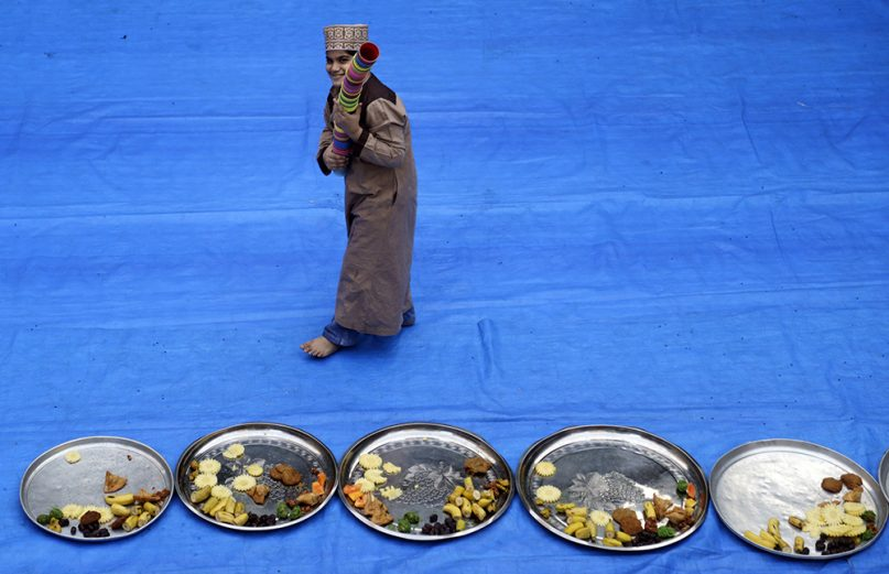 An Indian Muslim boy carries cups while helping prepare serving dishes for an iftar meal during the holy month of Ramadan in Mumbai, India, on May 16, 2019. (AP Photo/Rajanish Kakade)