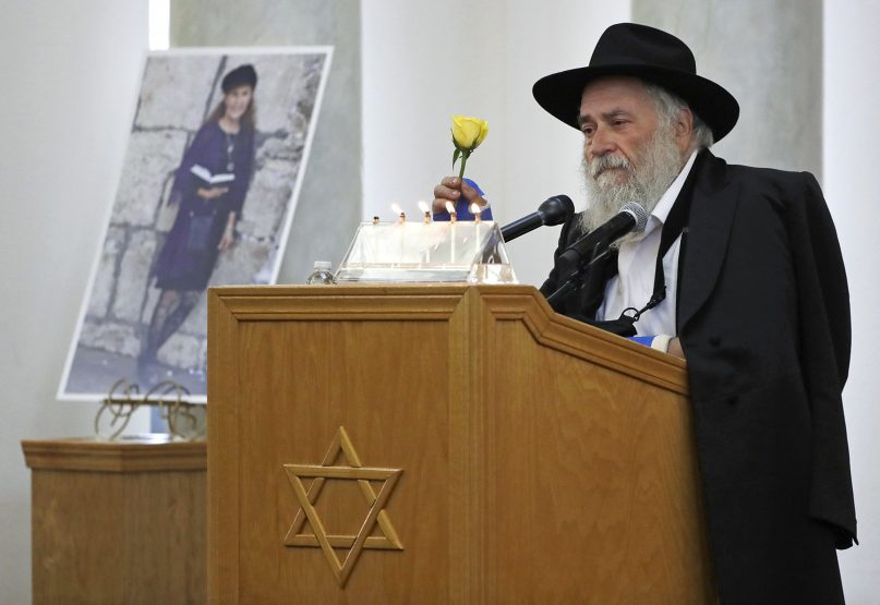 Yisroel Goldstein, rabbi of Chabad of Poway, holds a yellow rose as he speaks April 29, 2019, at the funeral for Lori Kaye, who is pictured at left, in Poway, Calif. Kaye, who was killed Saturday when a gunman opened fire inside the Chabad of Poway synagogue, had given Goldstein the flower as part of a bouquet the day before the shooting, which also injured Goldstein. (AP Photo/Gregory Bull)