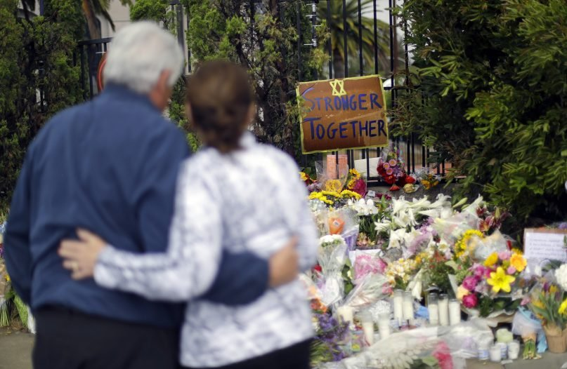 A couple embrace near a growing memorial across the street from the Chabad of Poway Synagogue in Poway, California, on April 29, 2019. A gunman opened fire two days before as about 100 people were worshipping, exactly six months after a mass shooting in a Pittsburgh synagogue. One person was killed in the Poway attack. (AP Photo/Greg Bull)