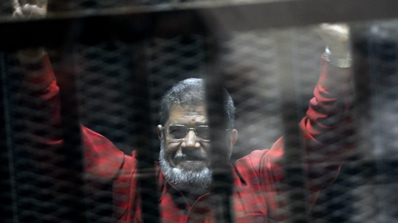 In this June 21, 2015 file photo, former Egyptian President Mohammed Morsi, wearing a red jumpsuit that designates he has been sentenced to death, raises his hands inside a defendants cage in a makeshift courtroom at the national police academy, in an eastern suburb of Cairo, Egypt. On Monday, June 17, 2019, Egypt's state TV said that the country's ousted President Mohammed Morsi has collapsed during a court session and died. (AP Photo/Ahmed Omar, File)