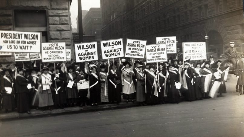 Women's suffrage activists wearing suffrage sashes demonstrate with signs on Oct. 20, 1916. Photo by Burke and Atwell/LOC/Creative Commons