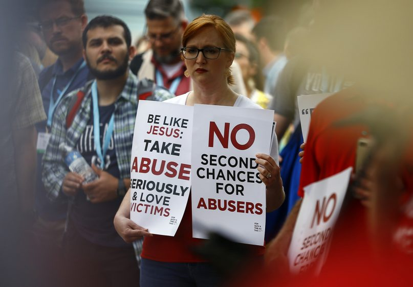A woman holds signs about abuse during a rally outside the annual meeting of the Southern Baptist Convention at the Birmingham-Jefferson Convention Complex on June 11, 2019, in Birmingham, Ala. RNS photo by Butch Dill