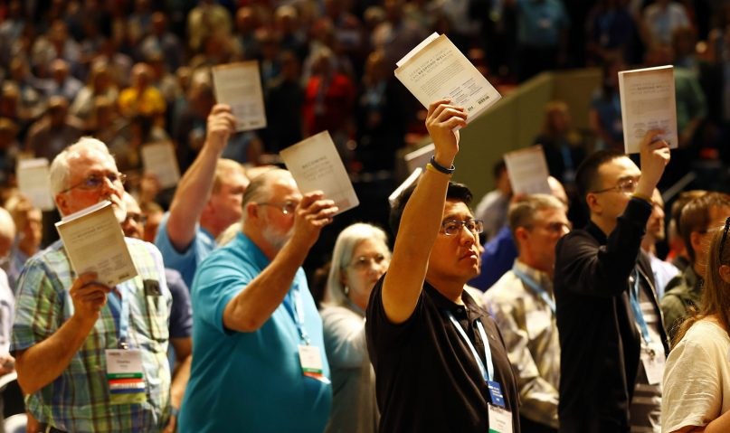 Messengers hold up an SBC abuse handbook while taking a challenge to stop sexual abuse during the annual meeting of the Southern Baptist Convention at the Birmingham-Jefferson Convention Complex on June 12, 2019, in Birmingham, Alabama. RNS photo by Butch Dill