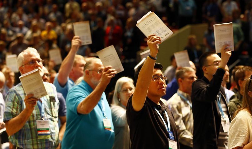 Messengers hold up SBC abuse handbooks while taking a challenge to stop sexual abuse during the annual meeting of the Southern Baptist Convention at the Birmingham-Jefferson Convention Complex, June 12, 2019, in Birmingham, Alabama.  RNS photo by Butch Dill