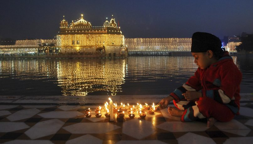 A young Sikh boy lights a candle at the Golden Temple, illuminated in the pre-dawn hours during the birth anniversary of Guru Nanak, the first Sikh guru, in Amritsar, India, on Nov. 17, 2013. (AP Photo/Prabhjot Gill)