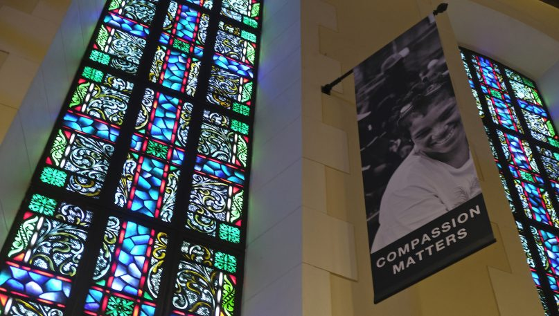 In this Feb. 12, 2019, file photo, a banner hangs by a stained-glass window in the sanctuary at Glide Memorial United Methodist Church in San Francisco. Most Americans don't typically reach out to religious leaders for guidance, according to a poll from The Associated Press-NORC Center for Public Affairs Research. The poll shows the lack of personal connection with ministers even includes people who identify with a religion, though it's less prevalent among those most engaged with their faith. (AP Photo/Eric Risberg)