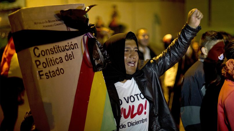 A protester holds a giant replica of Bolivia's constitution, wrapped with a black mourning ribbon, in La Paz, Bolivia, on Nov. 29, 2017. (AP Photo/Juan Karita)
