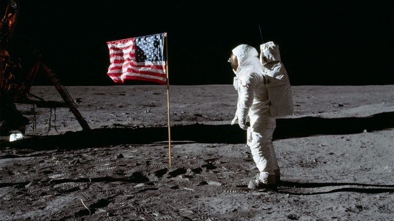 Astronaut Buzz Aldrin salutes the deployed United States flag during an Apollo 11 extravehicular activity on the lunar surface in July 1969. The lunar module is on the left, and the footprints of the astronauts are visible in the soil of the moon. Photo by Neil Armstrong/NASA/Creative Commons