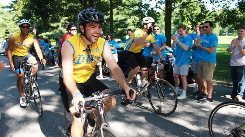 Jack Mannebach, a sophomore at St. Norbert College in Wisconsin, leads a group of 23 cyclist missionaries with Biking for Babies as they complete their ride on July 13, 2019, at Tower Grove Park in St. Louis. RNS photo by Eric Berger