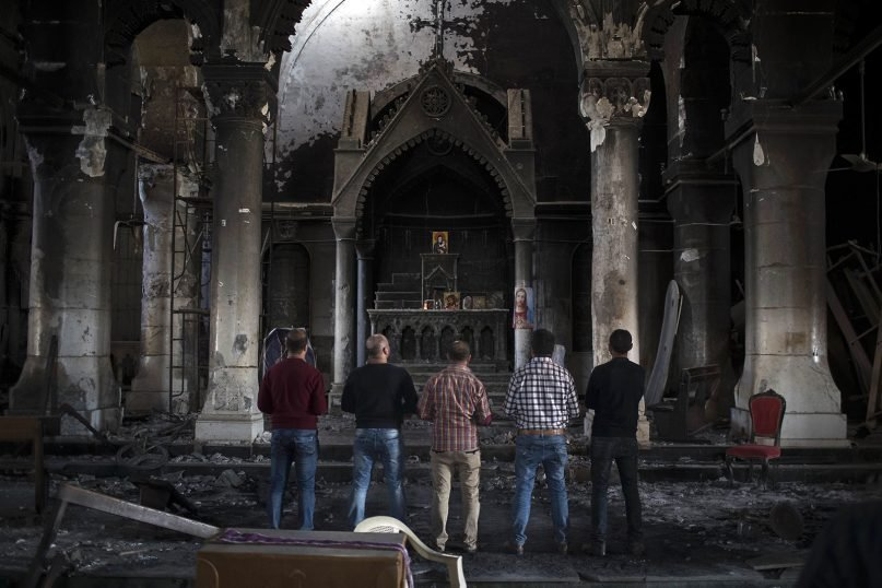Iraqi Christians pray at the Church of the Immaculate Conception, damaged by Islamic State fighters during their occupation of Qaraqosh, east of Mosul, Iraq, on Nov. 12, 2016. Qaraqosh, the biggest Christian town on the Nineveh Plains in Iraq's north, fell to the Islamic State group in 2014. (AP Photo/Felipe Dana)