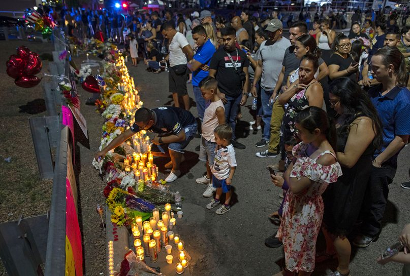 People gather at a makeshift memorial for the victims of Saturday's mass shooting at a shopping complex in El Paso, Texas, on Aug. 4, 2019. (AP Photo/Andres Leighton)