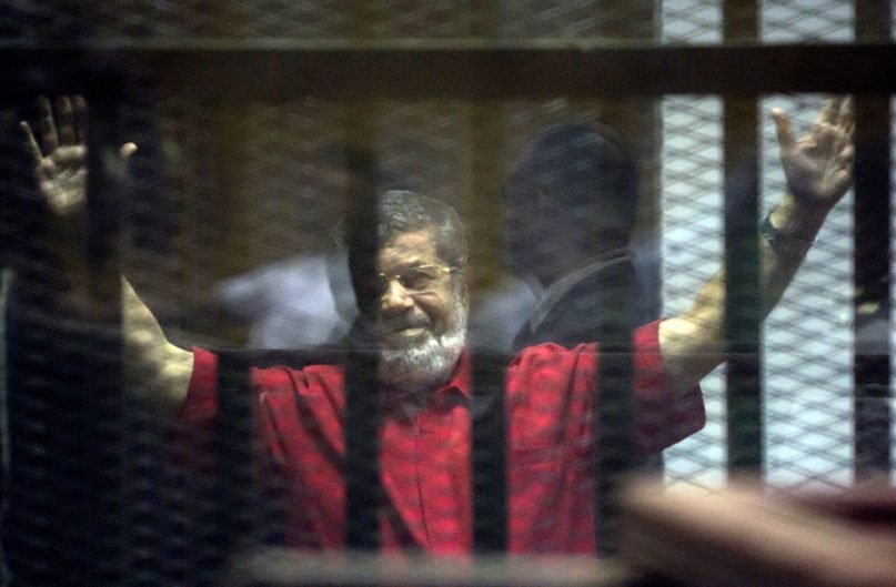 Former Egyptian President Mohammed Morsi, wearing a red jumpsuit that designates he has been sentenced to death, raises his hands inside a defendants cage in a makeshift courtroom at the national police academy in an eastern suburb of Cairo on June 18, 2016. Morsi was ousted by the military in July 2013 and died while on trial in June 2019. (AP Photo/Amr Nabil)