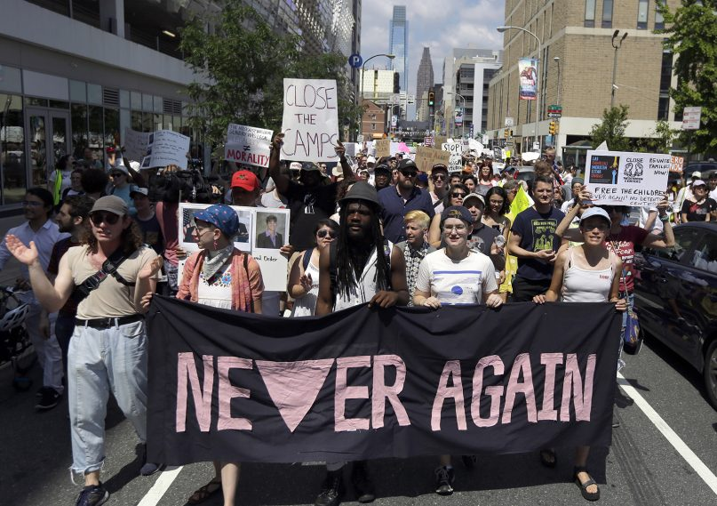 Protesters assembled by a majority Jewish group walk through traffic as they make their way to Independence Mall on July 4, 2019, in Philadelphia. Hundreds gathered during the city's traditional Fourth of July parade to protest the treatment of immigrants and asylum-seekers. (AP Photo/Jacqueline Larma)