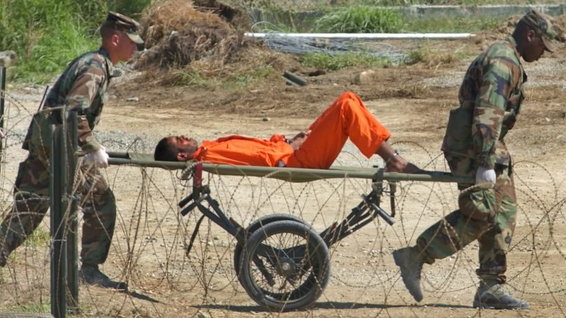 A detainee from Afghanistan is carried on a stretcher before being interrogated by military officials at the detention facility Camp X-Ray on Guantanamo Bay U.S. Naval Base in Cuba on Feb. 2, 2002. (AP Photo/Lynne Sladky)