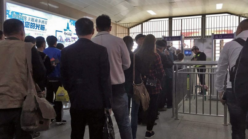Uighurs wait in line at a face scan checkpoint in Turpan, Xinjiang, in northwest China, on April 11, 2018. Photo by Darren Byler/Creative Commons